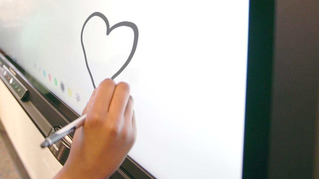 Eine Hand zeichnet ein Herz auf einem Promethean-Display